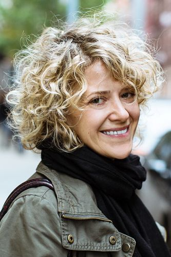 modern natural curly haircut for women over 50 to look younger