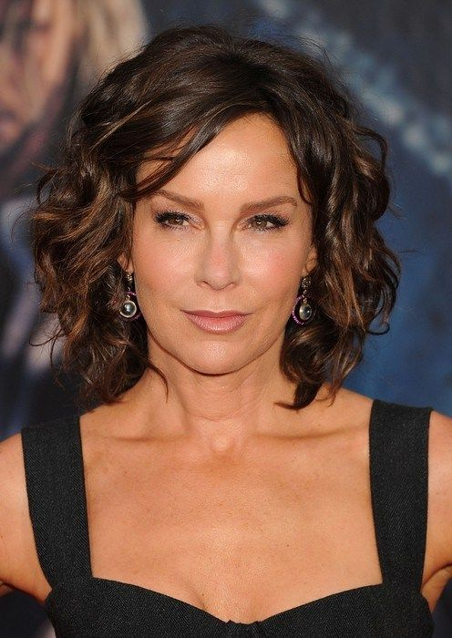 modern wavy curly haircut for women over 50 with thick hair